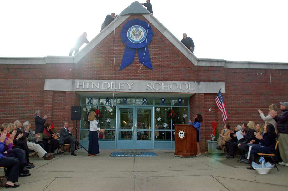 Hindley School fifth-grade teacher Katy Gale, left, and Principal Rita Ferri unveil on Wednesday, Dec. 5, the giant blue ribbon on the front of the building to mark that the school has been designated a National Blue Ribbon School by the U.S. Department of Education. The ribbon will adorn the building for five years. Photo: Contributed
