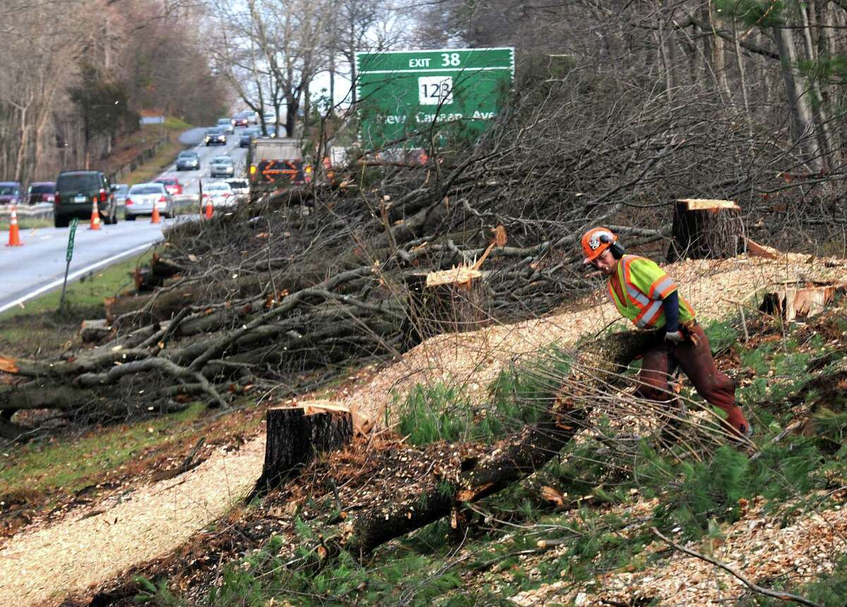 Connecticut DOT workers clear tree debris along the Merritt Parkway's northbound area just past the Marvin Ridge Rd. overpass in New Canaan, Conn. on Tuesday Dec. 11, 2012. The state has undertaken a comprehensive cutting effort to remove damaged and unhealthy trees. The effort has drawn the attention of a couple of conservation-minded parkway admirers but the DOT maintains that taking down potentially hazardous trees is necessary for safety reasons.