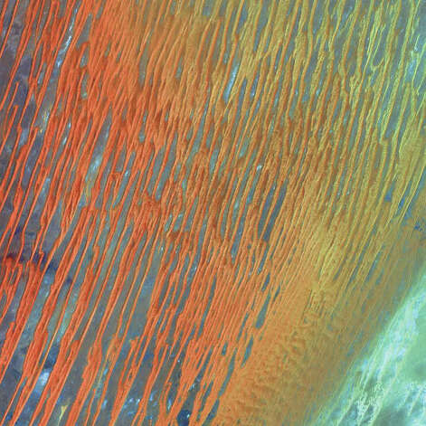 In this Landsat 7 image from 2003, the amber and caramel lattices seen are large, linear sand dunes in the Erg Chech dune sea located in the Sahara region of western Algeria. An erg, meaning dune field in Arabic, is a wide, flat area of desert covered with wind-blown sand and little vegetation cover. The dunes are formed when large amounts of transported sand are halted by topographic barriers. The largest dunes can take up to a million years to build. Ergs are also found on other celestial bodies such as Venus, Mars, and Saturn's moon Titan. Photo: NASA