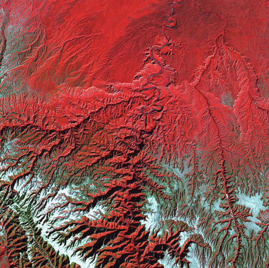 Nearly as deep as the Grand Canyon, Desolation Canyon is one of the largest unprotected wilderness areas in the American West. In this Landsat 7 image from 2000, the Green River in Utah flows south across the Tavaputs Plateau (top) before entering the canyon (center). Desolation Canyon has a rich history. Geologist and explorer John Wesley Powell named the canyon. During two river expeditions in 1869 and 1871, Powell's team mapped the Green River for the first time before heading down the Colorado River to the Grand Canyon. The U.S. declared Desolation Canyon a National Historic Landmark in 1968. Photo: NASA