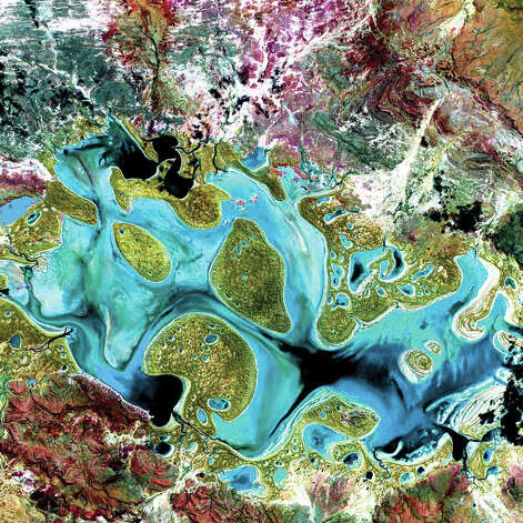 Ephemeral Carnegie Lake, in Western Australia, fills with water only during periods of significant rainfall. In dry years, it is reduced to a muddy marsh. When full, it can cover an area of about 6 square kilometers. In this Landsat 7 image from 1999, flooded areas appear dark blue or black. Vegetation appears in shades of dark and light green, and sands, soils, and minerals appear in a variety of colors. Photo: NASA