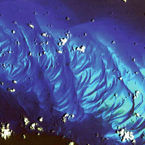 "In this 2002 Terra image, calcium carbonate sand dunes are apparent in the shallow waters of Tarpum Bay, southwest of Eleuthera Island in the Bahamas. The sand making up the dunes comes from the erosion of limestone coral reefs, shaped into dunes by ocean currents. Eleuthera Island is one of the larger ""out"" islands of the Bahamas. The island itself consists mainly of low, rounded limestone hills, and the highest elevation of the island is about 60 meters. It has a rough, karst topography with caves, sinkholes, and cenotes. The island is surrounded by coral reefs and pink sand beaches. Photo: NASA"