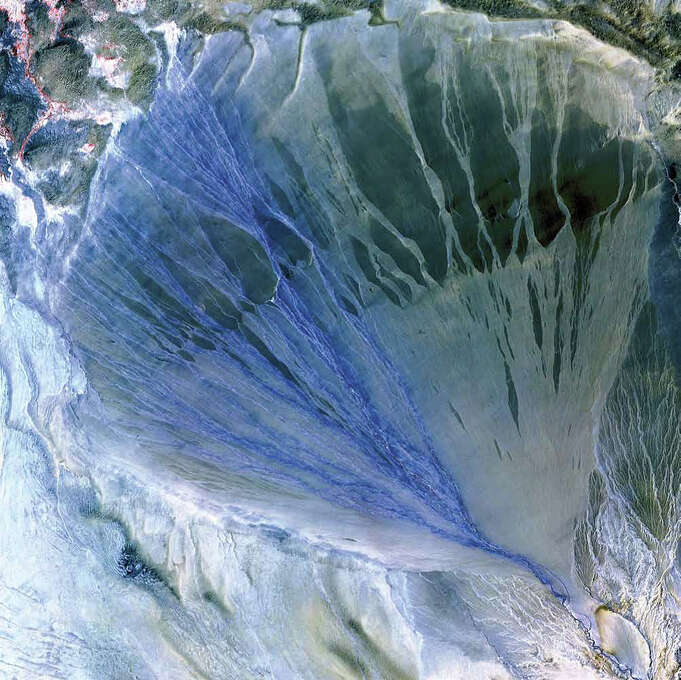 "A vast alluvial fan unfolds across the desolate landscape between the Kunlun and Altun mountain ranges that form the southern border of the Taklimakan Desert in China's Xinjiang Province. The fan is about 60 kilometers long and 55 kilometers wide at its broadest point. The left side is the active part of the fan. Water flowing down from the mountains in the many small streams appears blue in this 2002 image from the Terra satellite. Vegetation appears red and can be seen in the upper left corner of the image. Farmers take advantage of water at the foot of the fan to irrigate small fields. The ""lumpy"" terrain at the top of the image is composed of sand dunes at the edge of the Taklimakan, one of the largest sandy deserts on Earth. Photo: NASA"