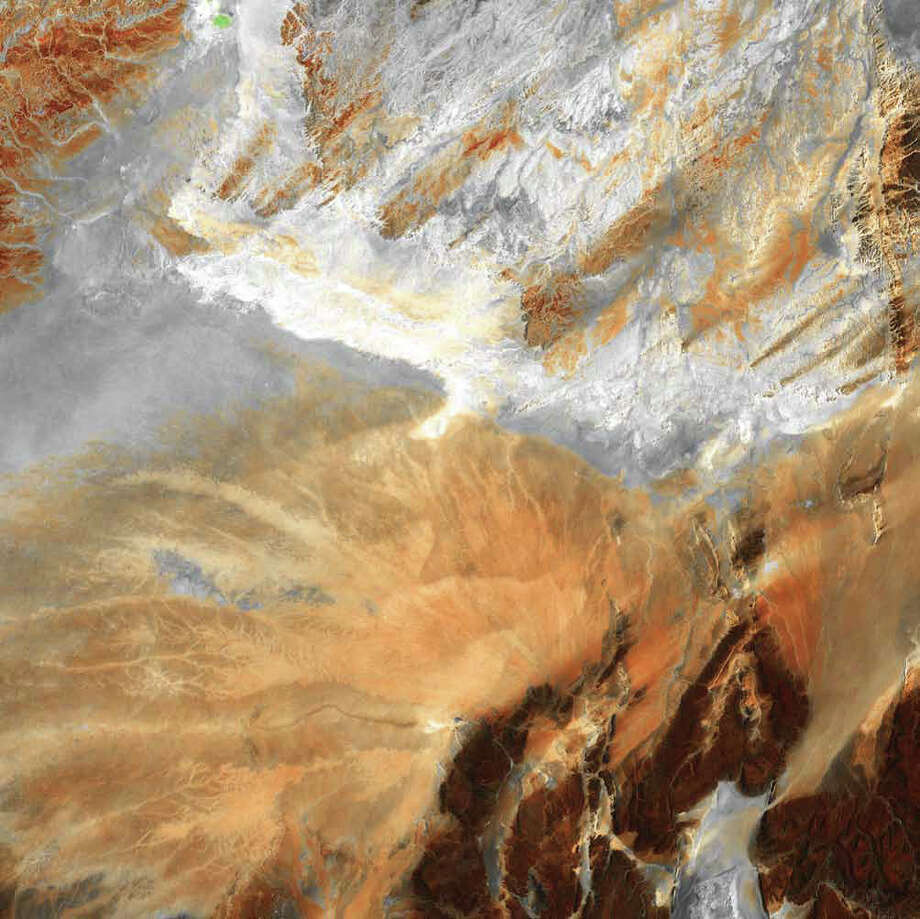 Lying amid the Great Eastern Erg, the Great Western Erg, and the Atlas Mountains in Northern Africa, the Sahara Desert in central Algeria is dotted by fragmented mountains (in brown, lower right) where barren, windswept ridges overlook arid plains. In this Landsat 5 image from 2009, a system of dry stream beds crisscrosses the rocky landscape awaiting the rare, intense rains that often cause flash floods. Photo: NASA