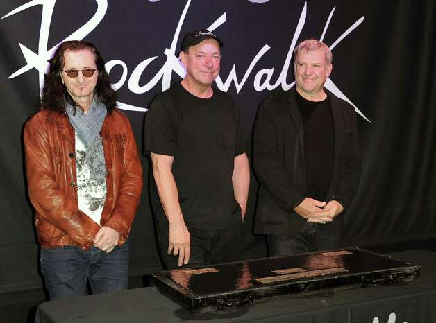 "FILE - This Nov. 20, 2012 file photo shows members of the band Rush, from left, Geddy Lee, Neil Peart, and Alex Lifeson at the RockWalk induction of Rush at Guitar Center in Los Angeles. The eclectic group of rockers Rush and Heart, rappers Public Enemy, songwriter Randy Newman, ""Queen of Disco"" Donna Summer and bluesman Albert King will be inducted into the Rock and Roll Hall of Fame next April in Los Angeles. The inductees were announced Tuesday by 2012 inductee Flea of The Red Hot Chili Peppers at a news conference in Los Angeles. (Photo by Richard Shotwell/Invision/AP, file) Photo: Richard Shotwell"