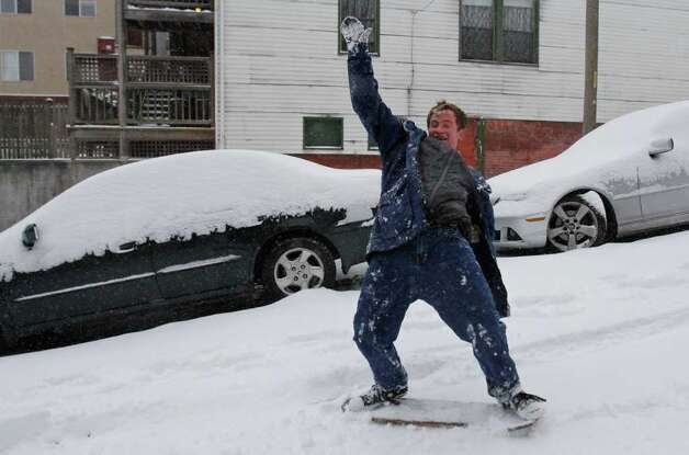 James Pentz attempts to ride a skateboard deck down Terrace St. in the First Hill neighborhood of Seattle on Wednesday, Jan. 18, 2012. Winter storms have rendered many Seattle streets unusable by cars. Photo: JOE DYER / SEATTLEPI.COM