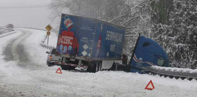 A semi-truck is shown after it left an off-ramp of Interstate-5 near Nisqually, Wash., during a snowstorm, Wednesday, Jan. 18, 2012. Heavy snow from a winter storm clogged roadways in the area and led to widespread school and business closures. Photo: Ted S. Warren / Associated Press