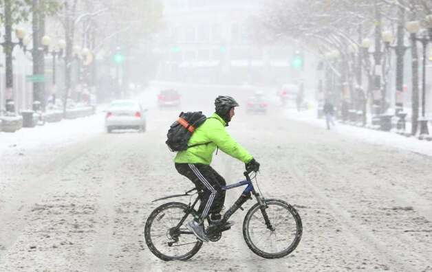 A bicycle commuter makes his way along Pike Street in downtown Seattle during a snowstorm on Wednesday, January 18, 2012 in Seattle. Photo: JOSHUA TRUJILLO / SEATTLEPI.COM