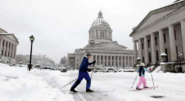 Amelia McHugh, 9, right, and her father, Noel McHugh, left, cross-country ski, Wednesday, Jan. 18, 2012, at the Capitol in Olympia, Wash. A winter storm dumped more than a foot of snow in Olympia and around the region, and provided the rare sight of the Capitol dome dusted with snow. Photo: Ted S. Warren / Associated Press