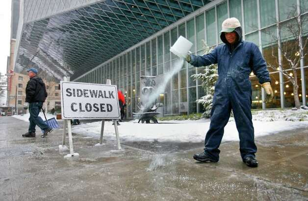 Seattle Public Library  worker Marlie Sersoze salts the sidewalks outside the Central Library on 4th Avenue on Wednesday, Jan. 18, 2012. Photo: LINDSEY WASSON / SEATTLEPI.COM
