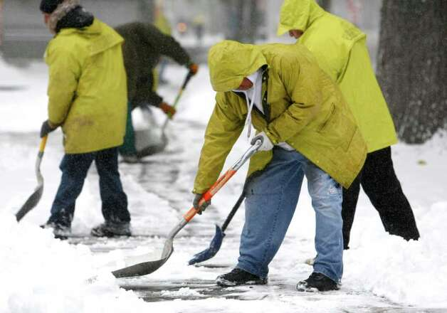 Members of a King County Community Work program shovel the sidewalk on Fourth Avenue on January 18, 2012 in Seattle, after a sno. Snow fell in the city, wreaking havoc with area roads and transit. Photo: JOSHUA TRUJILLO / SEATTLEPI.COM