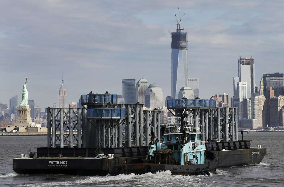 A barge loaded with sections of spire for One World Trade Center, center, is guided by tugboat across New York Harbor, Tuesday, Dec. 11, 2012 in New York. The Statue of Liberty is at left, and the Empire State Building is second left. Photo: Mark Lennihan, Associated Press