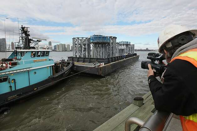 Sections of the crowning spire for One World Trade Center arrive on a barge on the Hudson River on December 11, 2012 in New York City. The barge is carrying nine pieces of steel that will eventually  top off One World Trade Center out at a symbolic 1,776 feet, becoming the tallest building in the Western Hemisphere. Photo: Mario Tama, Getty Images