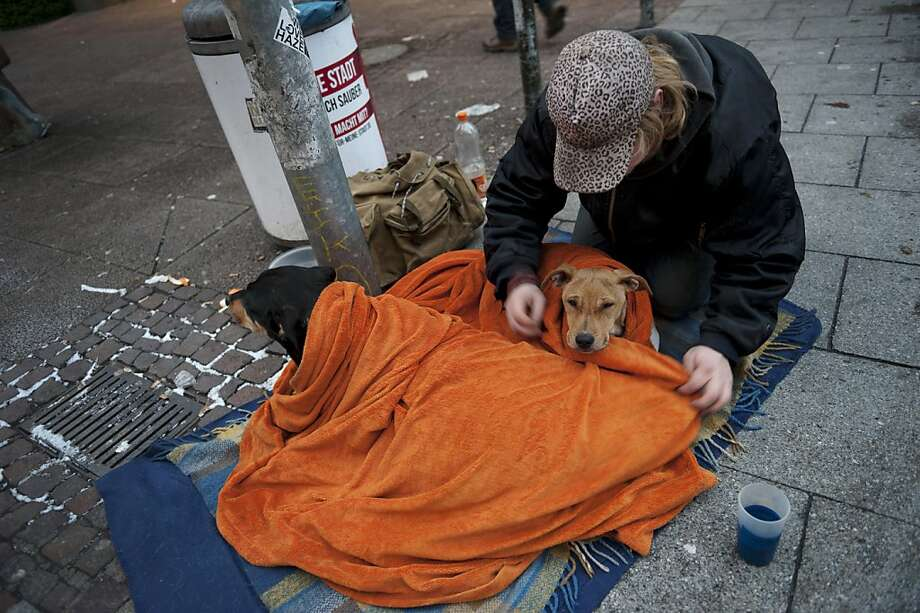 A beggar wraps his dog in blankets before asking passers-by for spare change in Hanover, Germany. Photo: Emily Wabitsch, AFP/Getty Images