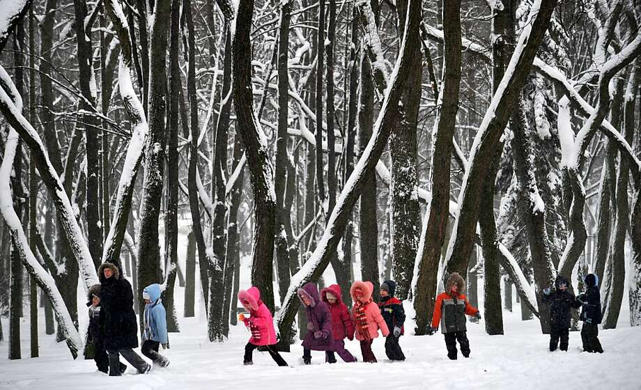 Children track through the new snow in a park in Minsk. Photo: Viktor Drachev, AFP/Getty Images