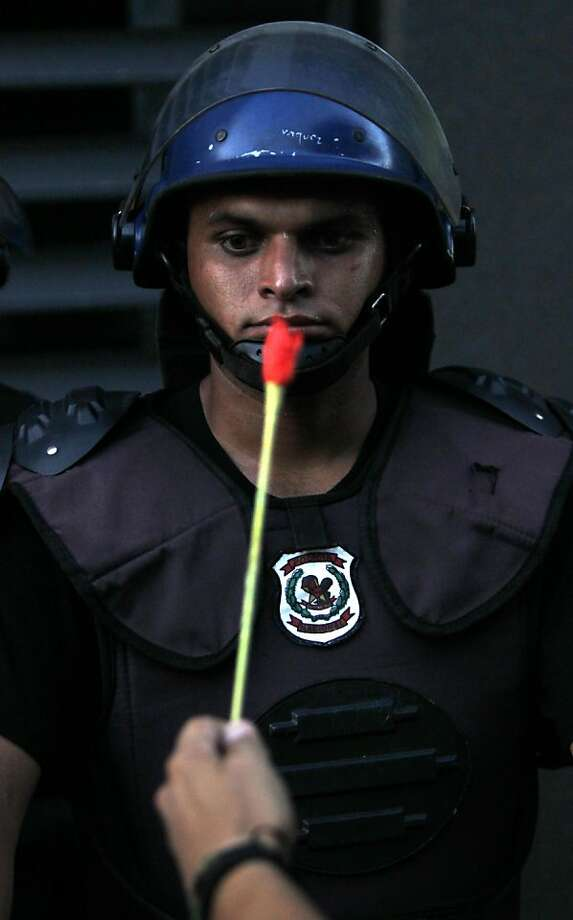 """A riot cop looks like he's counting to 10as an activist sticks a  flower in his face at  a demonstration marking International Human  Rights Day in Asuncion, Paraguay. The demonstrators were protesting the  treatment of prisoners and witnesses involved in """"the Massacre of  Curuguaty,"""" a violent land eviction on June 15 that left 11 peasants and  six police officers dead. Photo: Jorge Saenz, Associated Press"""