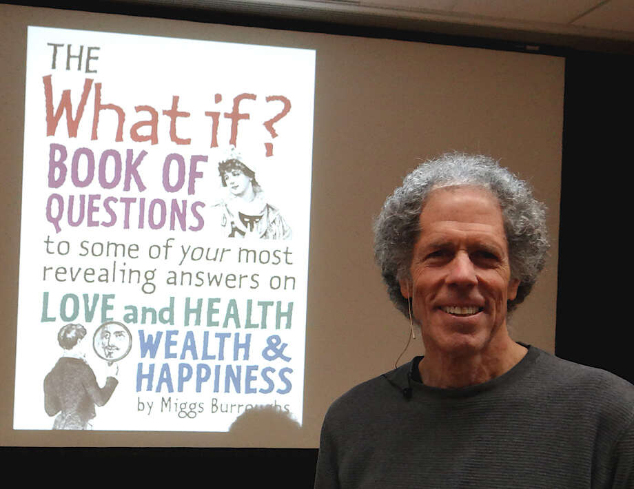 "Westport graphic artist and photographer Miggs Burroughs stands in front of the porjected image of the cover of his first book, ""The What If Book of Questions,"" which he discussed Monday at the Westport Public Library.  Westport CT 12/10/12 Photo: Mike Lauterborn / Westport News contributed"