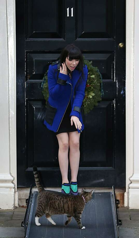 Pet me maybe: Singer Carly Rae Jepsen tries to make friends with Freya, the Chancellor of the Exchequer's cat, at Number 11 Downing Street in London. Chancellor of the Exchequer George Osborne is hosting his yearly Christmas party for the Starlight charity. Photo: Peter Macdiarmid, Getty Images