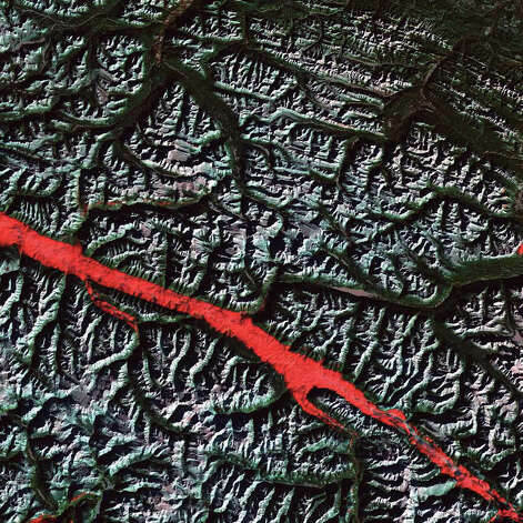 The stroke of red in this 2004 Landsat 5 image is a remarkable interplay of light and cloud in the Canadian Rockies. The Rocky Mountain Trench is a valley that stretches from the U.S. state of Montana to just south of Canada's Yukon Territory. It runs parallel with the peaks of the Canadian Rockies, ranging from 3 to 16 kilometers wide. Low clouds filled a part of the Trench near the border between the Canadian provinces of Alberta and British Columbia. The light-reflecting nature of the clouds coupled with low Sun elevation resulted in this startling effect. The Trench aligns with the Fraser River and makes its way past Mount Robson, the highest peak in the Canadian Rockies. Mount Robson is near the center of this image. Photo: NASA