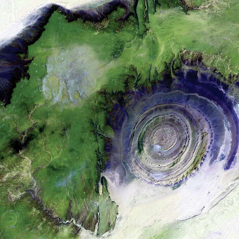 Viewed from space, the Richat Structure forms a conspicuous 50-kilometer-wide bull's-eye on the Maur Adrar Desert in the African country of Mauritania. Described by some as looking like an outsized fossil, the feature has become a landmark for astronauts. Although it resembles an impact crater, the structure formed when a volcanic dome hardened and gradually eroded, exposing the onion-like layers of rock. In this 2001 Landsat 7 image, desert sands appear white and pale yellow at the top left and lower right corners of the scene. Less sandy, rocky areas are green, and volcanic rocks are blue. Photo: NASA