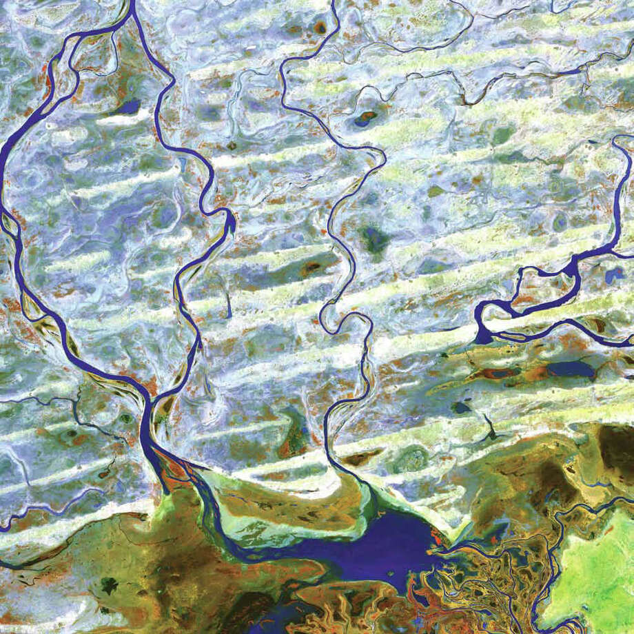 The Niger River and smaller rivers and streams flow northward out of Lake Debo in landlocked Mali in Western Africa. This region is part of the Inner Niger Delta, an intricate combination of lakes, river channels, and swamps with occasional areas of higher elevation. Known as the Macina, this wet oasis in the African Sahel is one of the largest wetlands in the world and provides habitat both for migrating birds and for West African manatees. This Terra image from 2003 shows the region during the dry season. On the right, water in rivers, streams, and lakes appears blue. On the left, the water turns greener, perhaps because of sediment. The reddish ridges running from east to west in the bottom half of the image are dunes. The pale-gray or white areas between the dunes are flat areas of silt, clay, or sandy soil. Blue shows where water has filled in between some of the dunes. Photo: NASA
