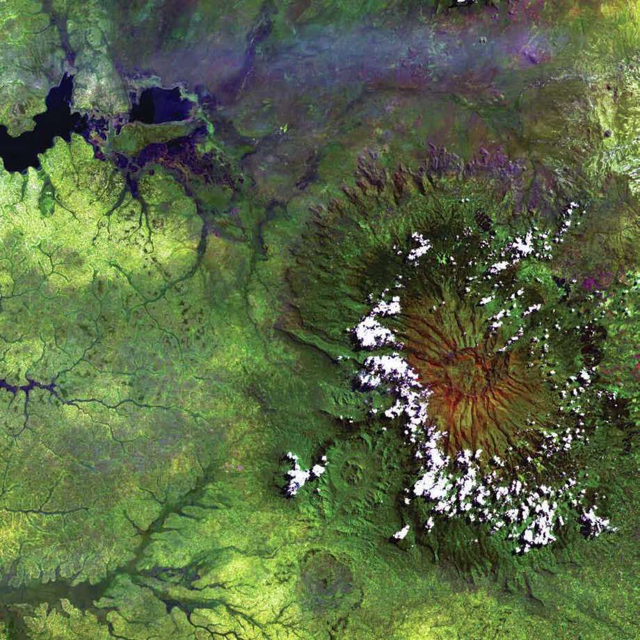 Clouds dot the high rim of Mount Elgon's massive caldera in this Landsat 5 image from 1984. As the oldest and largest solitary volcano in Africa, Mount Elgon straddles the border between Uganda and Kenya and is protected on both sides by national parks. Named Ol Doinyo Ilgoon by the Maasai, this long-extinct volcano has an intact caldera about 6,500 meters across and consists of five major peaks over a distance of 4,100 meters. In the image, the lush green that surrounds the volcano shows the fertility of the rich volcanic soil at the lower elevations. The upper left corner shows one of the arms of the large shallow lake complex of Lake Kyoga. Photo: NASA