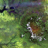 Clouds dot the high rim of Mount Elgon's massive caldera in this Landsat 5 image from 1984. As the oldest and largest solitary volcano in Africa, Mount Elgon straddles the border between Uganda and Kenya and is protected on both sides by national parks. Named Ol Doinyo Ilgoon by the Maasai, this long-extinct volcano has an intact caldera about 6,500 meters across and consists of five major peaks over a distance of 4,100 meters. In the image, the lush green that surrounds the volcano shows the fertility of the rich volcanic soil at the lower elevations. The upper left corner shows one of the arms of the large shallow lake complex of Lake Kyoga.