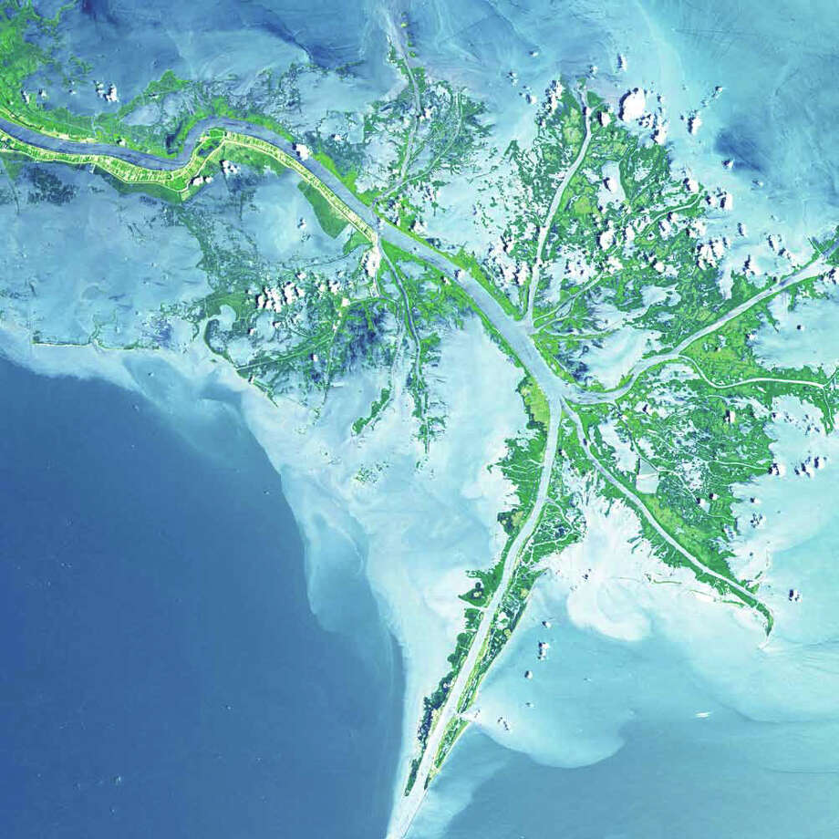After receiving the Arkansas and Red Rivers, the Mississippi River travels to its terminus and joins the Gulf of Mexico. The river's turbid waters spill out into the Gulf of Mexico, and its suspended sediment is deposited to form the Mississippi River Delta. As seen in this 2001 Terra image, marshes and mudflats (shades of green) prevail between shipping channels cut into the bird's-foot delta. The marshes protect the mainland from storm surges and provide a home for fish and wildlife. Photo: NASA