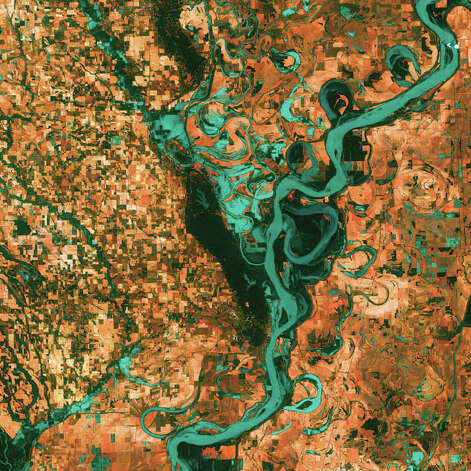 Graceful swirls and whorls of the Mississippi River encircle fields and pastures in this Landsat 7 image from 2003. Oxbow lakes and cutoffs accompany the meandering river south of Memphis, Tennessee, on the border between Arkansas and Mississippi. The mighty Mississippi is the largest river system in North America and forms the second largest watershed in the world. Photo: NASA