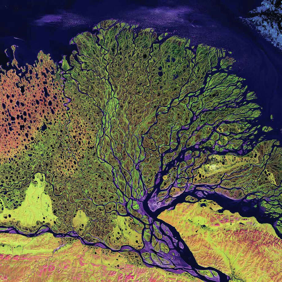 The Lena River Delta in Siberia extends 100 kilometers into the Laptev Sea and Arctic Ocean, and it includes an extensive protected wilderness area and wildlife refuge. In this Landsat 7 image from 2000, vegetation appears as shades of green, sandy areas as shades of red, and water as purples and blues. The Lena River Delta is about 400 kilometers wide, and it divides into a multitude of flat islands. The delta is frozen tundra for about 7 months of the year, and spring transforms the region into a lush wetland. Photo: NASA