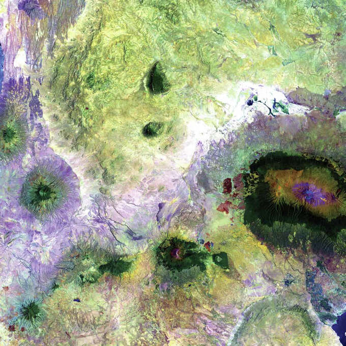 """Landsat 7 acquired this image of portions of Kenya and Tanzania in 2000. Featured on the far right is Mount Kilimanjaro, flanked by the plains of Amboseli National Park to the north and the rugged Arusha National Park to the south and west. Often called """"The Shining Mountain,"""" Kilimanjaro is a dormant stratovolcano. It has three volcanic cones—Kibo, Mawenzi, and Shira—and is the highest mountain in Africa. Although the mountain is located only about 300 kilometers from the equator, it has been capped by glaciers and snow for 11,000 years. This white cap shrinks and grows almost daily, and over the last century or more its overall trend has been a steady decline.  Photo: NASA"""