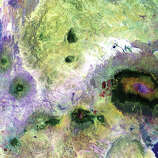 "Landsat 7 acquired this image of portions of Kenya and Tanzania in 2000. Featured on the far right is Mount Kilimanjaro, flanked by the plains of Amboseli National Park to the north and the rugged Arusha National Park to the south and west. Often called ""The Shining Mountain,"" Kilimanjaro is a dormant stratovolcano. It has three volcanic cones—Kibo, Mawenzi, and Shira—and is the highest mountain in Africa. Although the mountain is located only about 300 kilometers from the equator, it has been capped by glaciers and snow for 11,000 years. This white cap shrinks and grows almost daily, and over the last century or more its overall trend has been a steady decline."