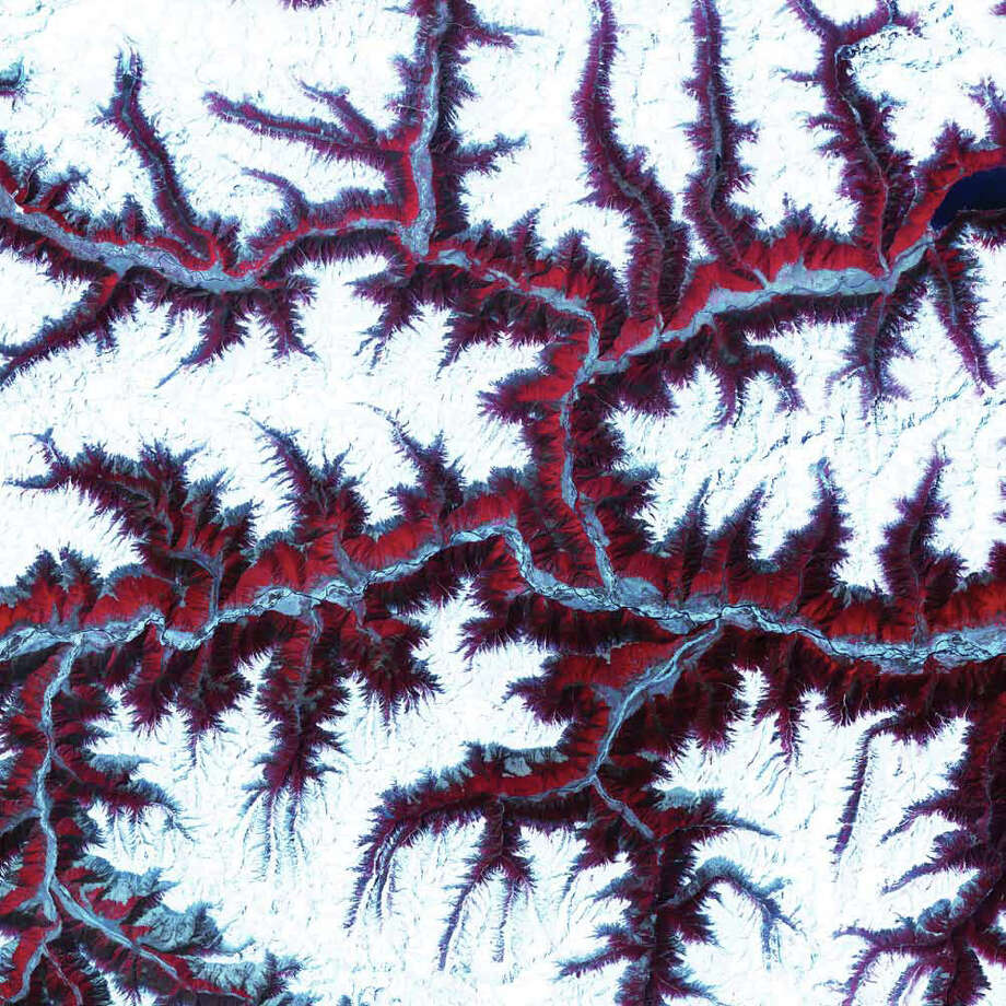 The soaring, snow-capped peaks and ridges of the eastern Himalaya Mountains create an irregular patchwork between major rivers in Tibet and southwestern China. Covered by snow and glaciers, the mountains here rise to altitudes of more than 5,000 meters. Vegetation at lower elevations is colored red in this Terra image from 2001. The Himalayas are made up of three parallel mountain ranges that together extend more than 2,900 kilometers. Uplift of the Himalayas continues today, at a rate of several millimeters per year, in response to the continuing collision of the Indian and Eurasian Plates that began about 70 million years ago. Photo: NASA
