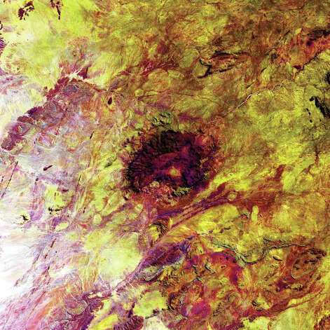 The dark heart in this Landsat 7 image from 2003 is the Erongo Massif, a prominent, sheer-walled semicircular mountain 30 kilometers in diameter. The massif rises 1,200 meters above the Namib Desert to the west and a mixed woodland savannah to the east. The mountain is an eroded relic of a volcano that was active some 140 to 150 million years ago but collapsed upon itself with the weight of the overlying magma. Eons of erosion by wind and wind-blown sand gradually exposed the long-dead volcano's core of granite and basalt. Minerals have been collected in the Erongo region for nearly 90 years, including some of the finest aquamarine, schorl, and jeremejevite.  Photo: NASA