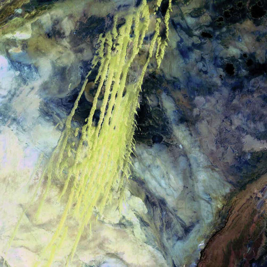 Ridges of wind-blown sand flow across Erg Iguidi, a Saharan sand sea. Erg Iguidi is one of several Saharan ergs and extends from Algeria into Mauritania in northwestern Africa. The dunes (in yellow) are about 250 meters wide, rising high above the sand sea. Winds blow from the northwest to the southeast, often under the influence of oceanic monsoons. In this 1985 Landsat 5 image, dunes in the center and upper left lie atop black sandstone rock while the light blue and white areas are edges of the chalk plateaus in the region. Photo: NASA