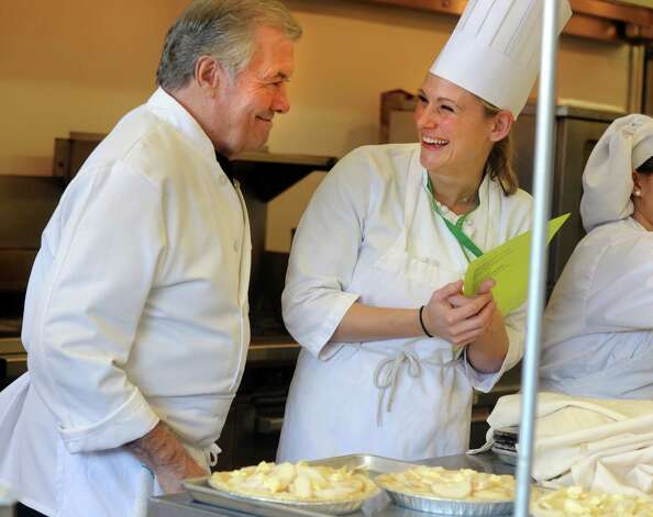 Chef Jacques Pépin chats with Culinary Department head Heather Priest during a visit to Emmett OíBrien Technical High School Tuesday, Dec. 11, 2012.  Pépin and students cooked more than 90 meals together for the Spooner House, a Shelton nonprofit that provides emergency shelter, meals, and services to families in the Naugatuck Valley. Photo: Autumn Driscoll / Connecticut Post