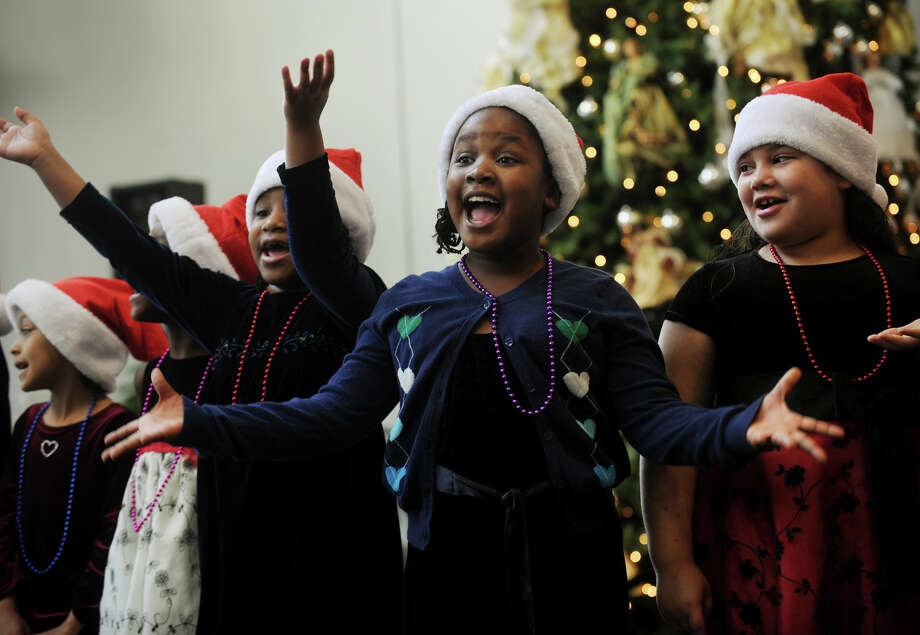 From left; Chanise Ninnott, 7, Kalei Hill, 7, and Angelis Hernandez, 8, second graders  in Candie Veccharelli's class at Wilbur Cross School in Bridgeport, perform in the lobby of St. Vincent's Hospital in Bridgeport on Tuesday, December 11, 2012. Photo: Brian A. Pounds / Connecticut Post