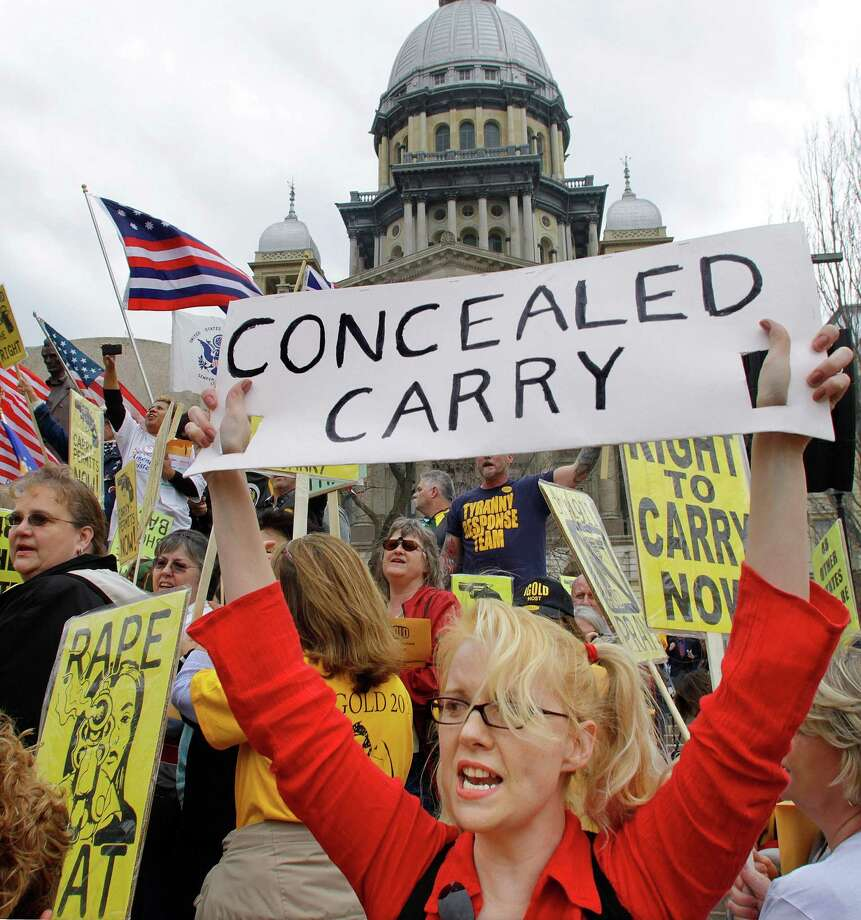 FILE - In this March 7, 2012 file photo, gun owners and supporters participate in an Illinois Gun Owners Lobby Day rally at the Illinois State Capitol in Springfield. In a big victory for gun rights advocates, a federal appeals court on Tuesday, Dec. 11, 2012, struck down a ban on carrying concealed weapons in Illinois _ the only remaining state where carrying concealed weapons is entirely illegal.  (AP Photo/Seth Perlman, File) Photo: Seth Perlman, STF / AP