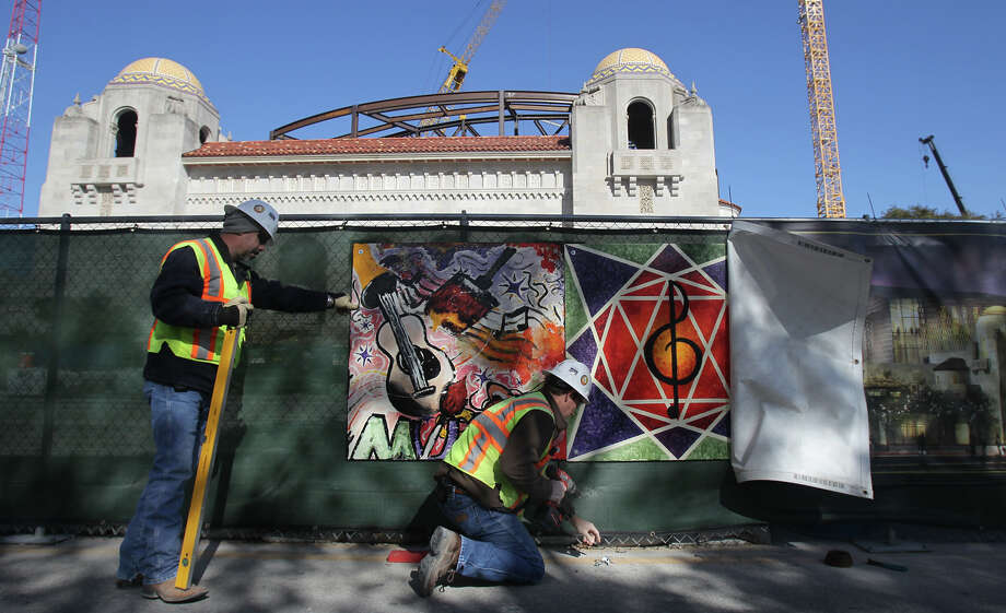 Randen Sheehan (left) and Ben Paschal of Linbeck Zachry attach works of art created by SAISD students and teachers to a fence at the Tobin Center for the Performing Arts. Photo: JOHN DAVENPORT, San Antonio Express-News / ©San Antonio Express-News/Photo Can Be Sold to the Public