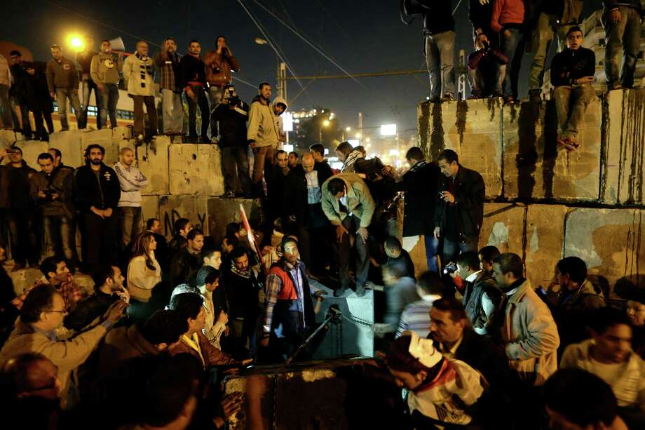 Protesters dismantle a wall of concrete blocks in front of the presidential palace during a demonstration Tuesday against President Mohammed Morsi in Cairo. Photo: Hassan Ammar, STF / AP