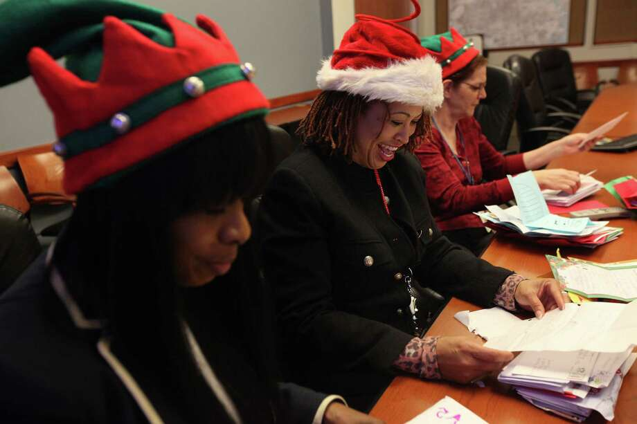 "Tara Woods smiles as she reads a child's wish list as Dionne Montague and Michelle Barrow Degomez, open and sort though Santa letters that arrived today from the Beaumont and Houston area for the ""Letters to Santa"" operation. Photo: Mayra Beltran, Houston Chronicle / © 2012 Houston Chronicle"