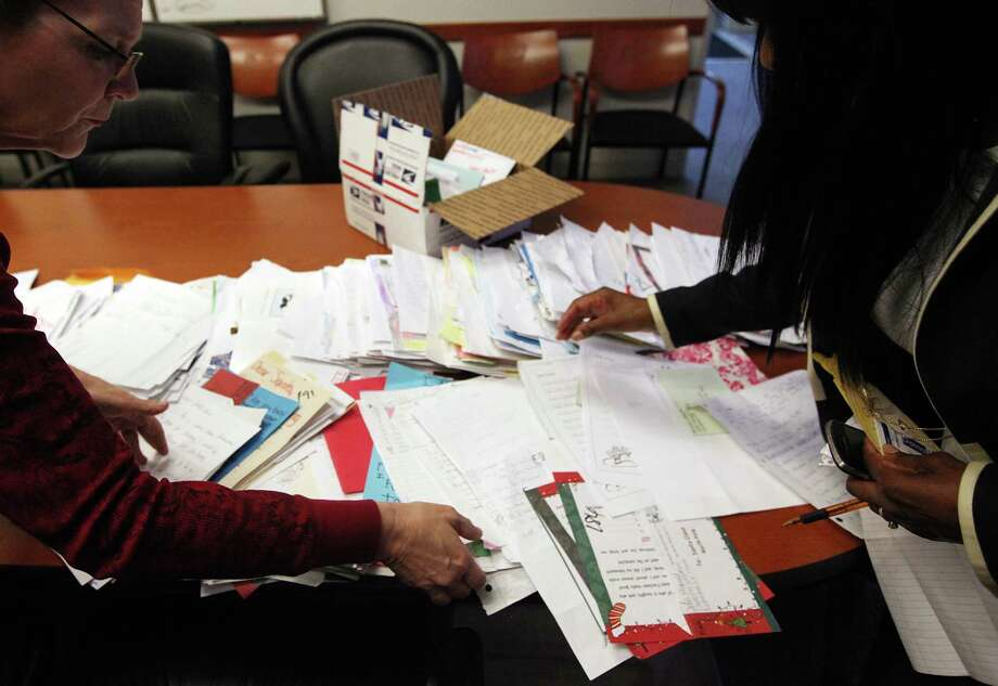 Michelle Barrow Degomez views some of  Santa letters volunteers have sorted through to determine which are need based letters at the Houston District Post Office on Tuesday, Dec. 11, 2012, in Houston. Photo: Mayra Beltran, Houston Chronicle / © 2012 Houston Chronicle