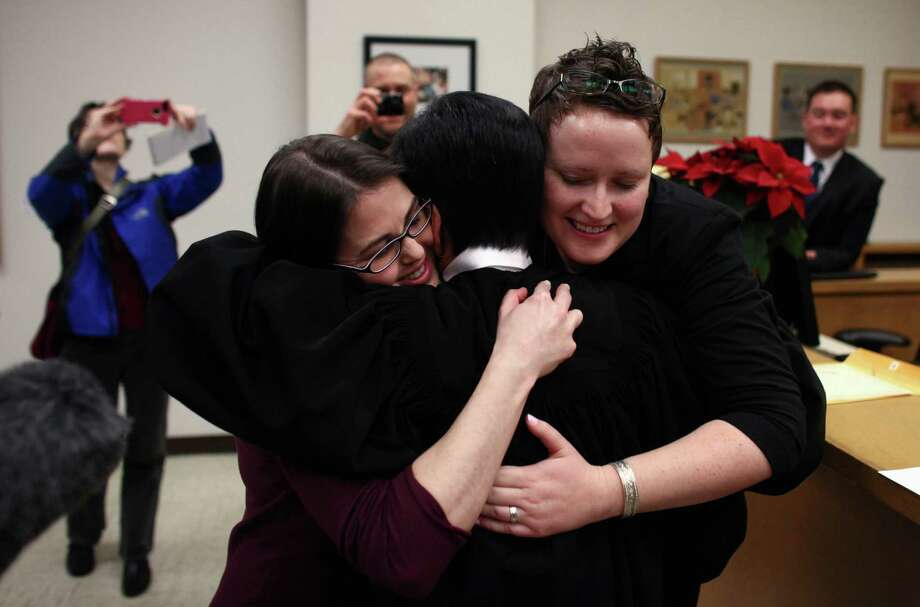 Emily Cofer, left, and Sarah Cofer, both of Arlington, hug  Superior  Court Judge Mary Yu as they are married by Yu just after midnight on  Sunday at the King County Courthouse in Seattle. Photo: JOSHUA TRUJILLO / SEATTLEPI.COM