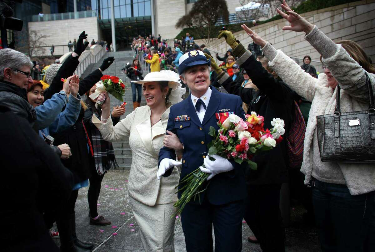 Deb Needham, left, and Nancy Monahan, a retired member of the U.S. Coast Guard, walk down the stairs of Seattle City Hall after they were married.