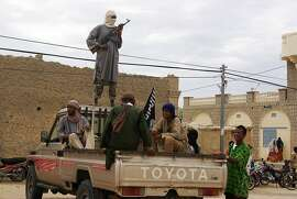 In this Aug. 31, 2012 file photo, fighters from Islamist group Ansar Dine stand guard in Timbuktu, Mali, as they prepare to publicly lash a member of the Islamic Police found guilty of adultery.  France is moving surveillance drones to western Africa amid rising concerns that an al-Qaida offshoot and its allies who control northeast Mali represent a major threat to French interests abroad _ and possibly at home. With six French hostages held by Islamic militants in the region, France is facing a delicate task, but has garnered support from other Western powers including the United States to keep Mali from becoming a new launchpad for global terrorism. (AP Photo, File)