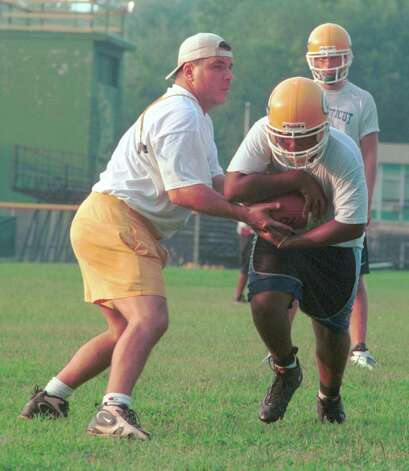 Trinity Catholic assistant football coach Pete Stokes hands off to Jeff Smith during the first day of practice on Aug. 20, 2001. Stokes stepped down as head coach Tuesday after four years at the helm Photo: Stephen Daniel/For The Advocate