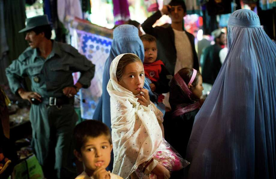A young Afghan girl shops with her mother in a crowded bazaar in Lashkar Gah, southern Helmand's provincial capital, on Oct. 23.  After 11 years of war, residents of southern Helmand are frustrated by the widespread insecurity. Photo: Anja Niedringhaus, STF / AP