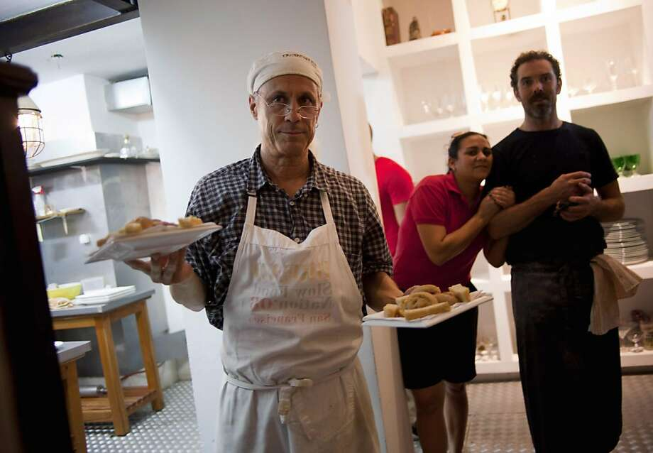 """Steve Sullivan holds plates of bread as Charlie Hallowell (right) surveys the dining room at Le Chansonnier in Havana. Sullivan and Hallowell were part of the """"Planting Seeds"""" delegation. Photo: Ramon Espinosa, Associated Press"""