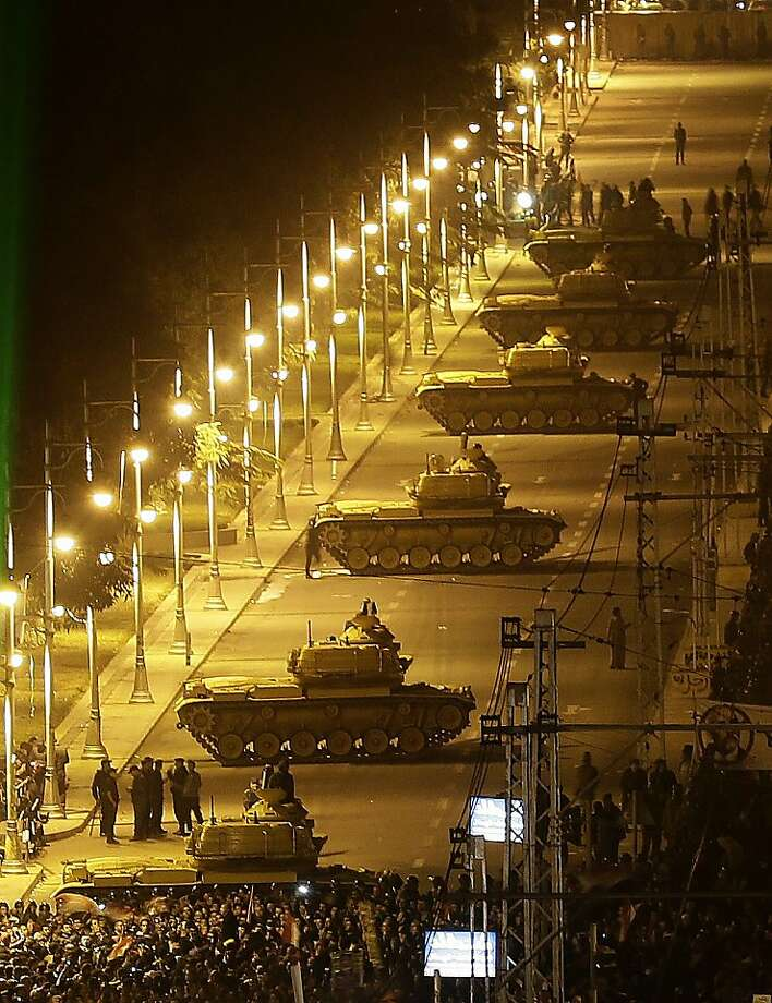 Egyptian Army tanks, left, deploy outside the presidential palace as Egyptian protesters gather during a demonstration against President Mohammed Morsi in Cairo, Egypt, Tuesday, Dec. 11, 2012. Thousands of opponents and supporters of Egypt's Islamist president staged rival rallies in the nation's capital Tuesday, four days ahead a nationwide referendum on a contentious draft constitution. (AP Photo/Hassan Ammar) Photo: Hassan Ammar, Associated Press