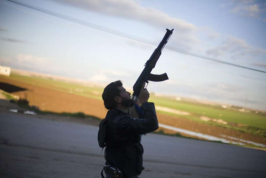 A Free Syrian Army fighter points his weapon as he watches a Syrian Army jet, not pictured, in Fafeen village, north of Aleppo province, Syria, Tuesday, Dec. 11, 2012. (AP Photo/Manu Brabo) Photo: Manu Brabo, Associated Press